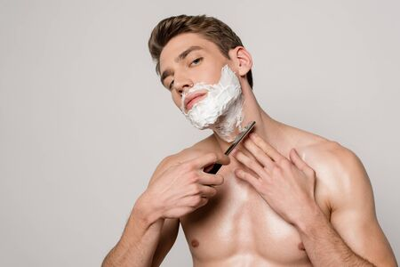 sexy man with muscular torso shaving with straight razor isolated on grey Stock fotó - 138254874