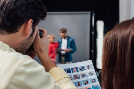 back view of photographer taking photo of model and art director in photo studio Banco de Imagens - 138254878