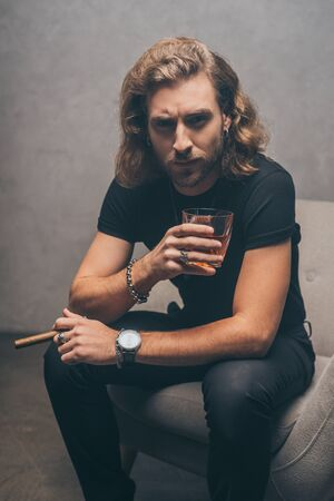 fashionable businessman in black outfit smoking cigar and drinking whiskey  in armchair near grey wall