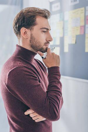 side view of pensive businessman holding marker pen