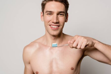 smiling sexy man with bare torso holding toothbrush isolated on grey Banque d'images