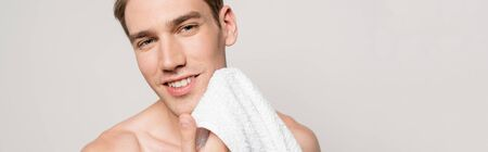 smiling sexy man with muscular torso holding cotton towel isolated on grey, panoramic shot