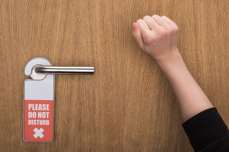 cropped view of woman knocking at door with please do no disturb sign Zdjęcie Seryjne