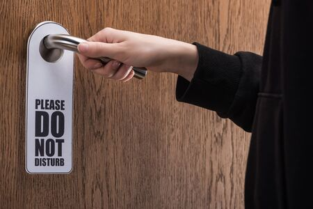 cropped view of woman holding door handle with please do no disturb sign