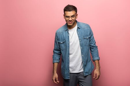 Handsome tricky man looking at camera on pink background Stock Photo
