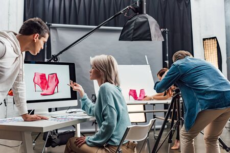 attractive art director gesturing near computer monitor with photo of shoes Banco de Imagens - 138255081