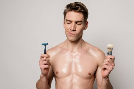 thoughtful sexy man with muscular torso holding shaver and shaving brush isolated on grey