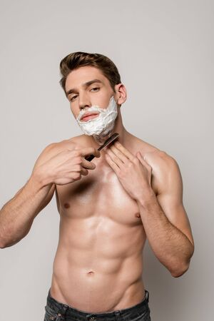 sexy man with muscular torso shaving with straight razor isolated on grey Stock fotó - 138255103