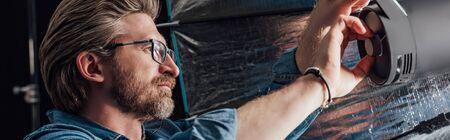 panoramic shot of bearded art director touching reflector in photo studio