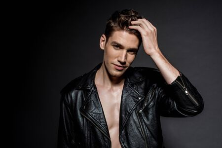 handsome young man in biker jacket touching hair on black background