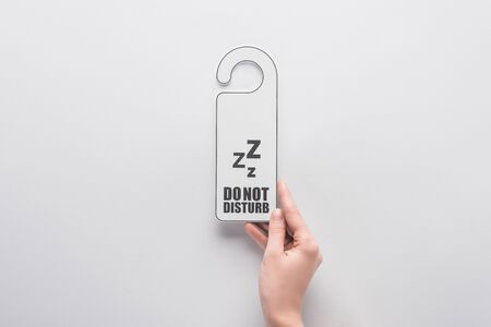 cropped view of woman holding do no disturb sign on white background