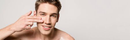 smiling sexy man with bare torso touching clean face isolated on grey, panoramic shot