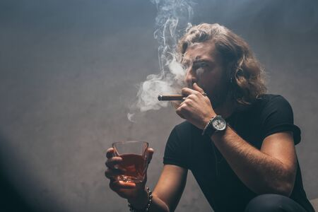 fashionable businessman in black outfit smoking cigar and drinking whiskey near grey wall