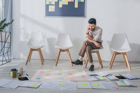pensive mixed race businessman sitting on chair near sticky notes Stock Photo