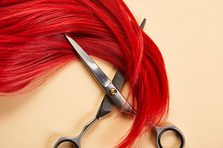 Top view of red hair and scissors on beige background 版權商用圖片