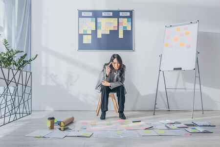 pensive asian scrum master sitting on chair near gadgets and sticky notes