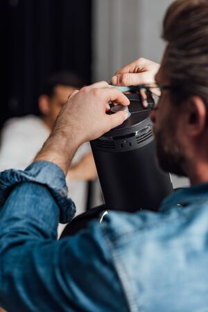 selective focus of bearded man touching reflector photo studio