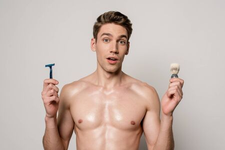 shocked sexy man with muscular torso holding shaver and shaving brush isolated on grey Stock fotó