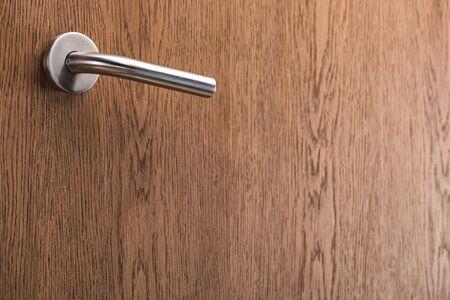 wooden hotel room door with metal handle