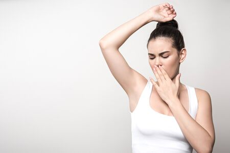 shocked woman looking at underarm and covering mouth with hand isolated on grey
