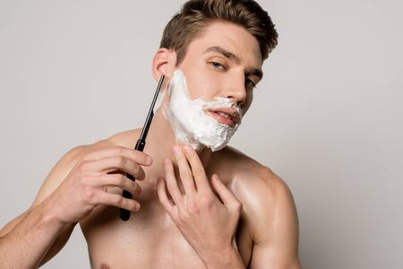 sexy man with muscular torso shaving with straight razor isolated on grey