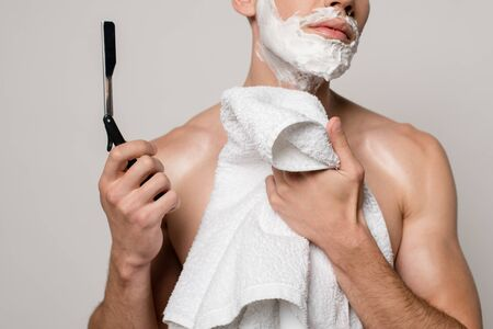 cropped view of sexy man with muscular torso and shaving foam on face holding straight razor and towel isolated on grey