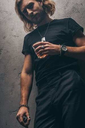 low angle view of fashionable businessman in black outfit with cigar and whiskey near grey wall