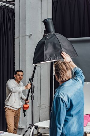 handsome assistant holding reflector near art director in photo studio