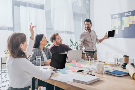 bi-racial scrum master looking at businesswoman with raising hand near coworkers
