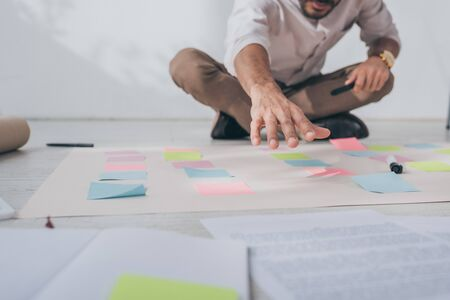 cropped view of mixed race businessman sitting with outstretched hand near sticky notes on floor