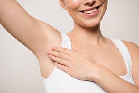 partial view of smiling woman applying deodorant on underarm isolated on grey