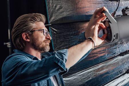 bearded art director touching reflector in photo studio