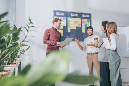 selective focus of scrum master using laptop near board with letters and multicultural coworkers