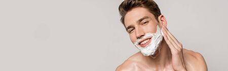 smiling man with muscular torso applying shaving foam isolated on grey, panoramic shot