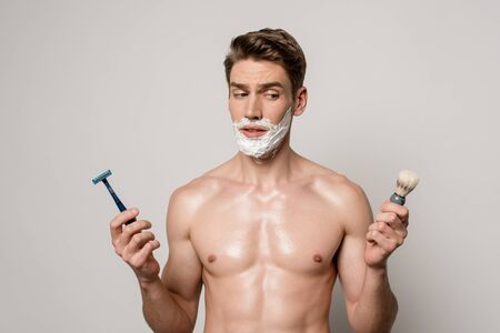 sexy man with muscular torso and shaving foam on face holding shaver and shaving brush isolated on grey 스톡 콘텐츠