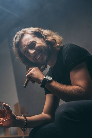 low angle view of laughing fashionable businessman in black outfit smoking cigar and drinking whiskey
