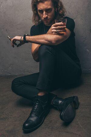 fashionable businessman in black outfit sitting on floor with cigar and whiskey near grey wall Zdjęcie Seryjne