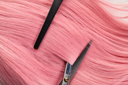 Top view of clip and scissors on colored pink hair on white background