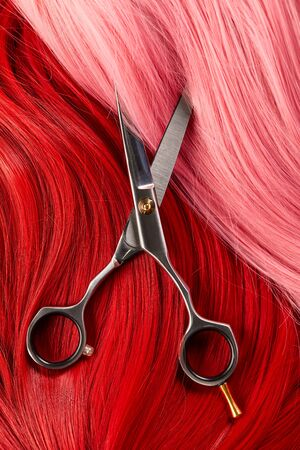Top view of red and pink hair with scissors