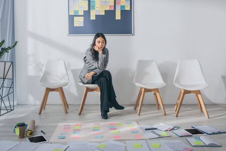 beautiful asian scrum master sitting on chair near gadgets and sticky notes