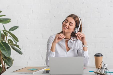 happy businesswoman listening music in headphones while relaxing in office