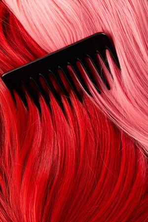 Top view of comb on colored pink and red hair 版權商用圖片