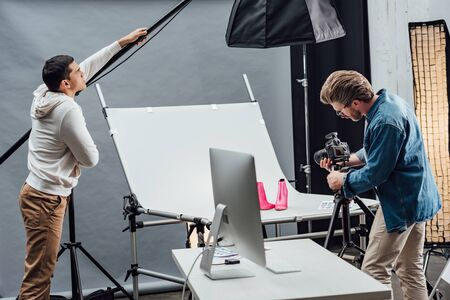 handsome assistant touching reflector while photographer photo shooting shoes Imagens
