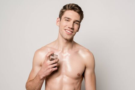 smiling sexy man with muscular torso spraying perfume isolated on grey