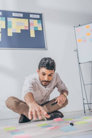 selective focus of mixed race scrum master sitting with outstretched hand near sticky notes on floor