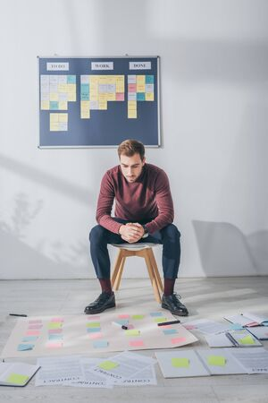handsome scrum master sitting with clenched hands near sticky notes Stock Photo