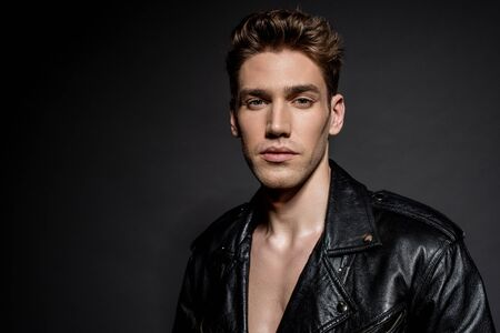 sexy young man in biker jacket on black background