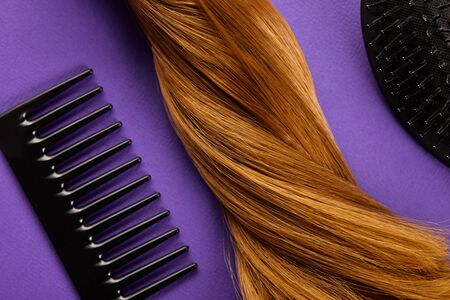 Top view of brown hair with comb and hairbrush on purple background Stock fotó