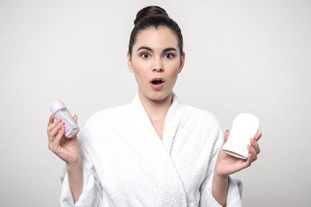 surprised woman in bathrobe holding deodorants while looking at camera isolated on grey