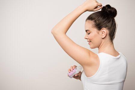 smiling woman applying deodorant on underarm isolated on grey Stock Photo